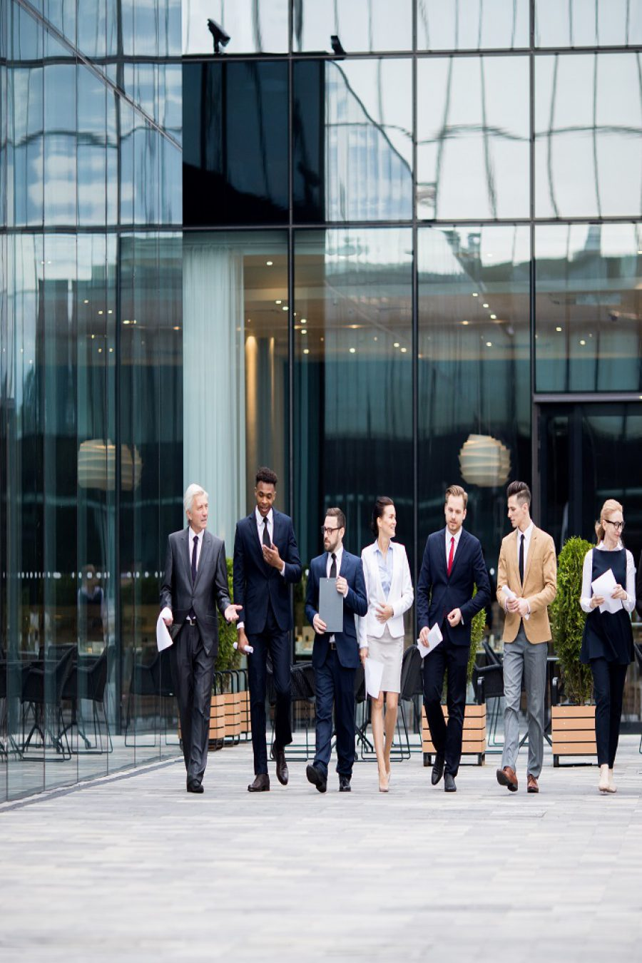 Large group of business people walking along modern business center and talking in urban environment