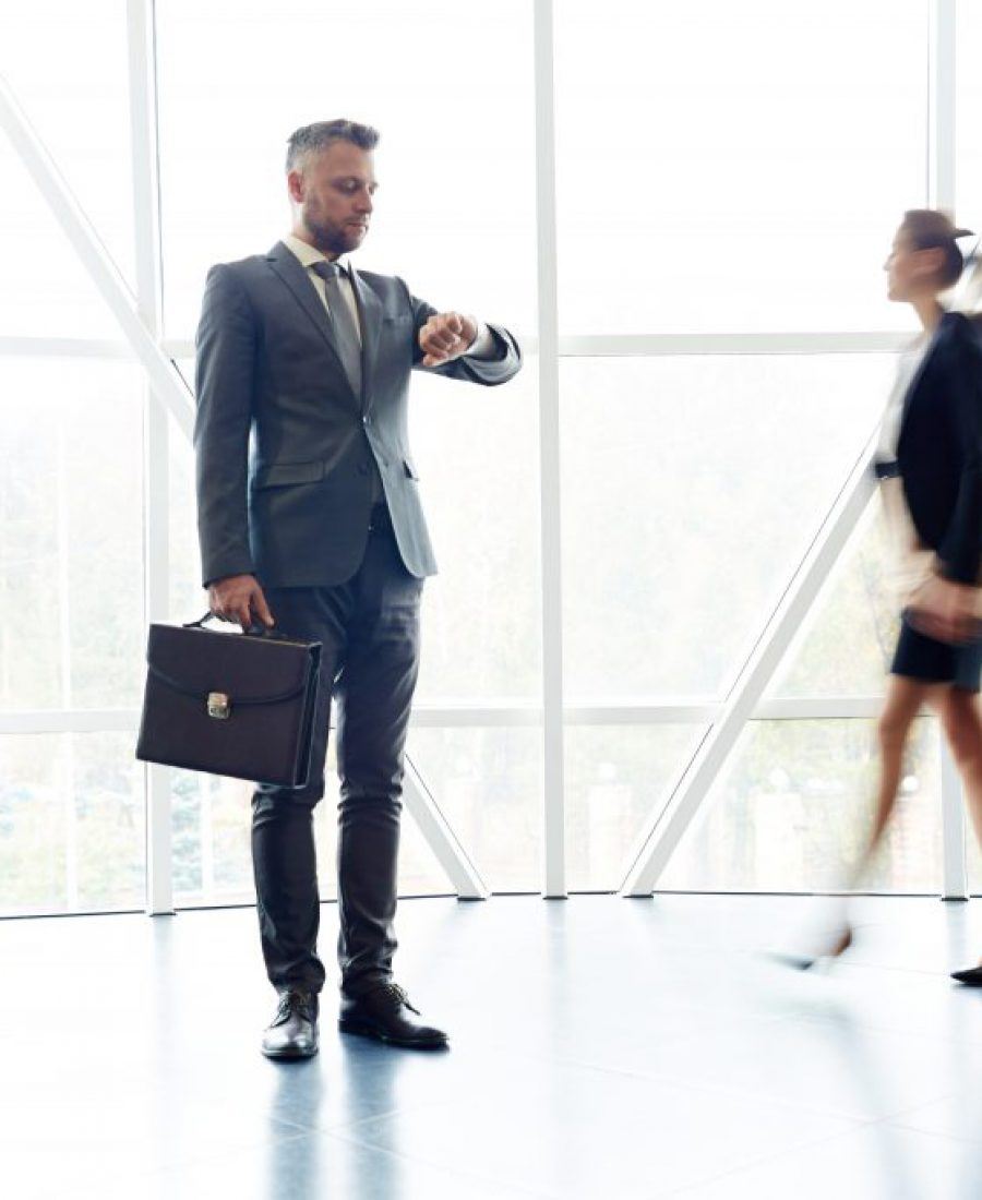Businessman with briefcase looking at wristwatch